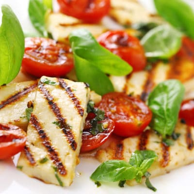 Grilled halloumi cheese with roasted tomatoes and basil
