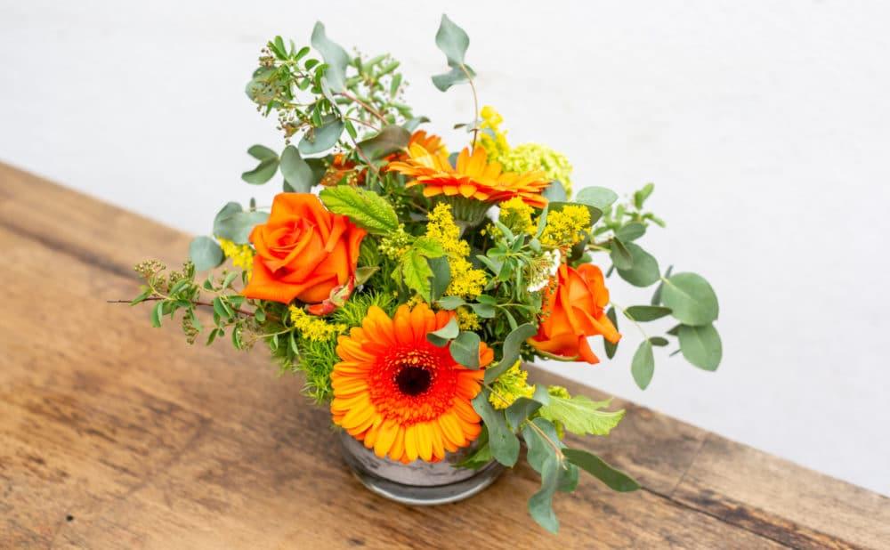 Mini gerbs, roses, solidago, dianthus & eucalyptus in a cylinder vase.