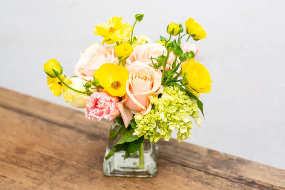 Butterfly ranunculus, roses, tulips & green hydrangeas in a clear vase.