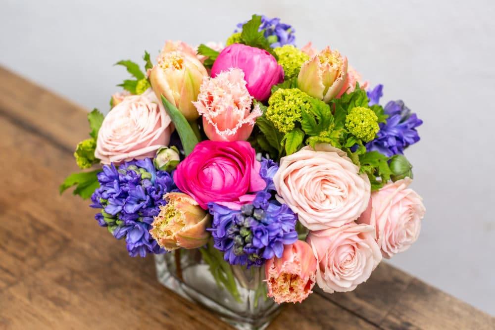Tulips, ranunculus, viburnum & spray roses in a cube vase.