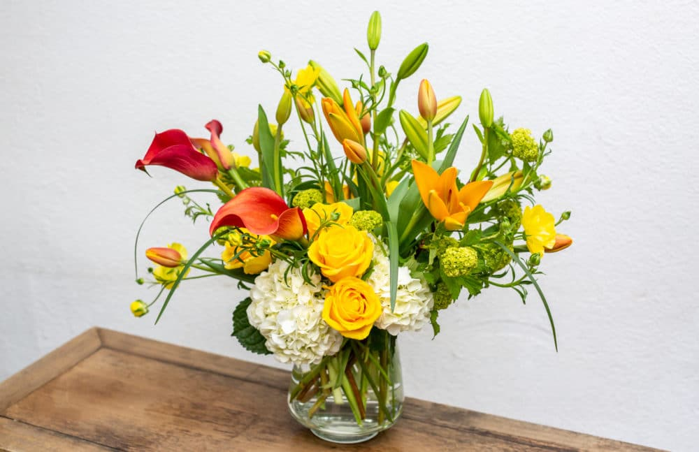 Yellow roses accented with lilies, hydrangeas & Oregon-grown calla lilies in a clear vase