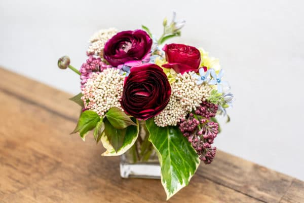 Ranunculus, rice flower & lilacs in a rectangular vase.