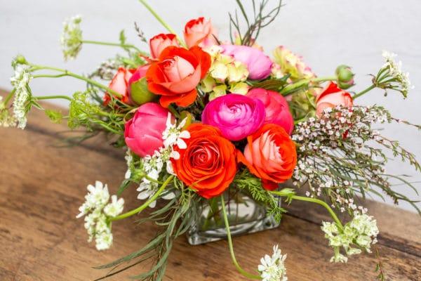 Spray roses, spirea & ranunculus in a cube vase.