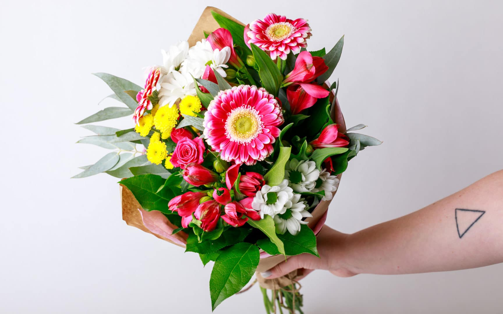 person holding a pink floral arrangement for Mother's Day from Zupan's Markets