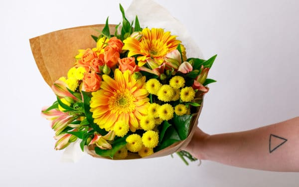person holding a yellow Mother's Day floral bouquet from Zupan's Markets
