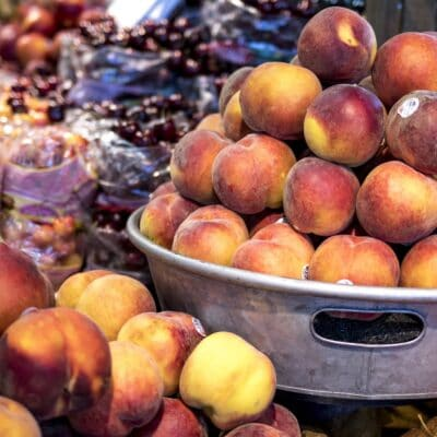 Metal bowl of fresh peaches