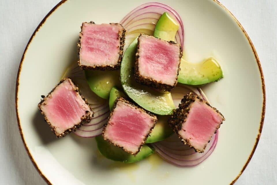 Seared Peppercorn Crusted Ahi Tuna over red onions and avocado