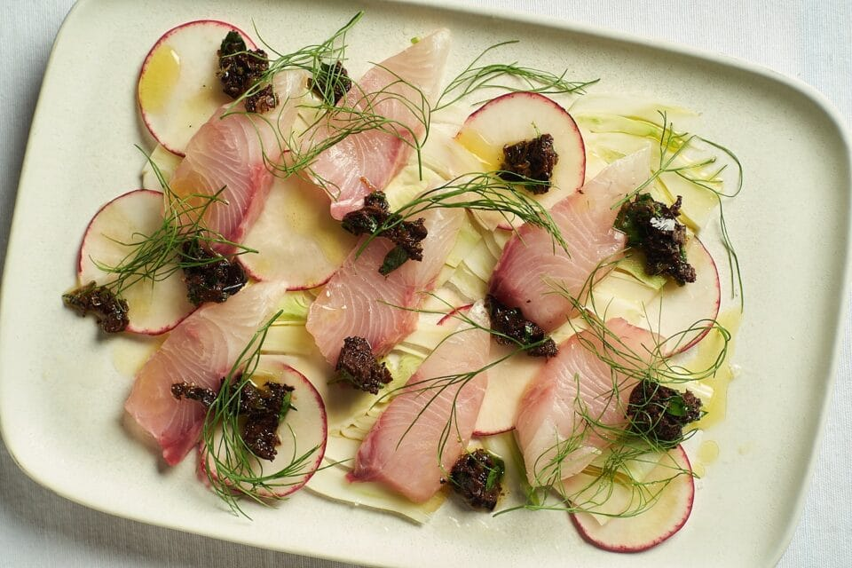 Kanpachi sashimi over shaved fennel topped with olive tapenade