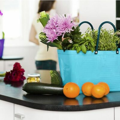 Hinza tote bag on a counter filled with flowers and produce