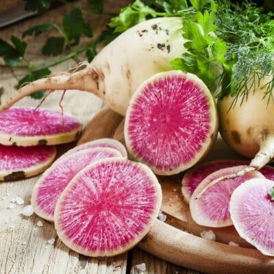 Cut pink radish, vintage wooden background