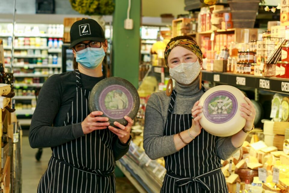 two Zupan's Markets employees holding wheels of cheese
