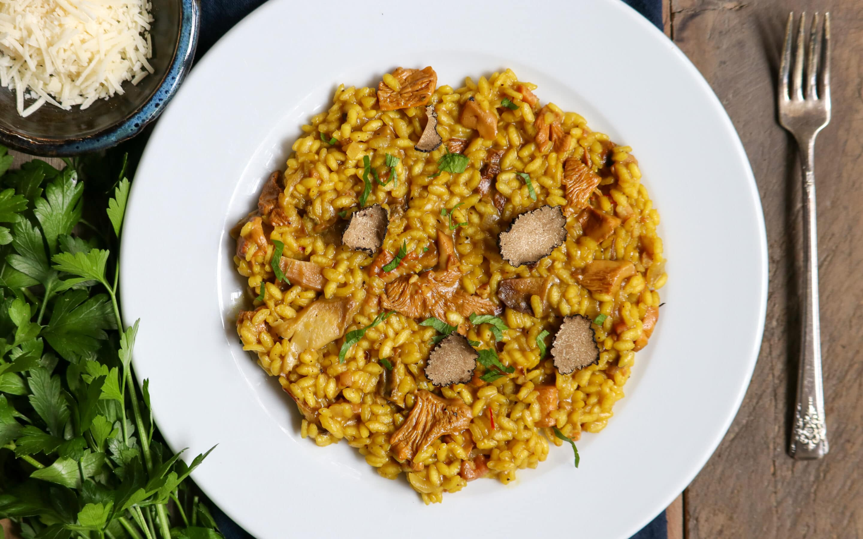 Chanterelle Mushroom risotto in a white bowl on a dinner table